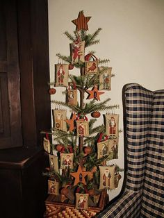 Prairie Schooler Santas Cross Stitch Handmade Ornaments ~ Beautifully displayed on a primitive country Christmas tree accented with rusty jingle bells and stars.  The black and cream check wing chair adds to the warmth and cozy decor....I am not fond of Santa, but posed to show the cute idea....