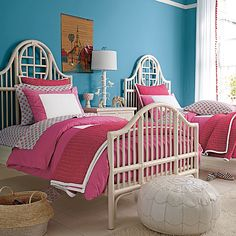 White wicker bed against a striking blue wall and accented with fuschia bedding