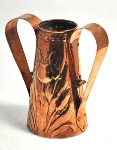 A large Arts and Crafts Newlyn copper twin handled vase embossed with Iris and with high loop handles, stamped to base, height 27cm.