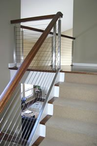 Interior cable railing with wood top and stainless steel posts