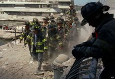Firefighters carry an injured fireman from the World Trade Center area after the buildings collapse. (AP Photo/Matt Moyer, File)