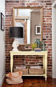 Exposed brick. cream table. large mirror. lamp. small storage underneath