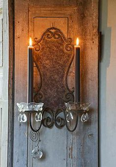 Candle sconce on shutters in restored farmhouse in the Loire valley