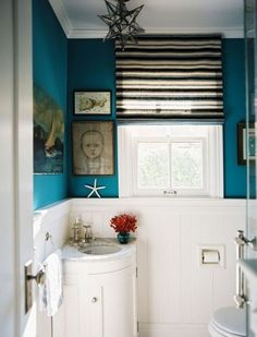 Teal wall color with original art and roman shade hung at ceiling level makes small bathroom seem larger.  Corner sink.