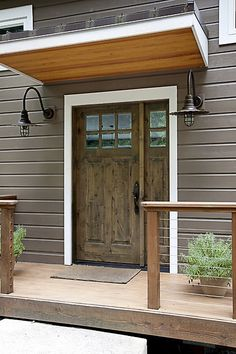 Simple stunning front door design with iron sconces and a small deck. Front Door Overhang, Front Deck, Front Porches, Front Doors, Front Entry, Front Gate Design, Main Door Design, House With Porch, House Front
