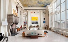 This NYC penthouse has white furniture, floral pillows, walls of glass, high ceilings, a ceiling mural and an eclectic and extensive art collection.