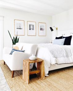 bright white bedroom with natural rug and gold picture frames