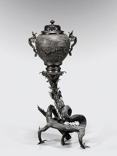 """Tall and antique, Japanese bronze temple censer; the base comprised of a large writhing three-clawed dragon; surmounted with a bulbous tapered vase, ornately decorated with birds in flowering branches in relief, and mounted with two-dragon-fish handles; H: 30 1/2""""; openwork wood cover"""