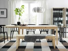 A dining room with NORNÄS dining table in pine wood and IKEA PS TORPET chairs in black... Love chairs + bench with table + sheepskin