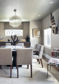 We created a dramatic custom square rift oak table with book matched top and hand chiseled edge for this modern dining room. Channel tufted chairs were designed in line with the tailored look. The wenge built-in buffet with a honed black stone top creates continuity with the adjacent living room fireplace through the repetitious use of materials. Sparkling mica wall covering on the ceiling provides a little shimmer and the vintage glass rod chandelier delivers a shot of understated glamour.