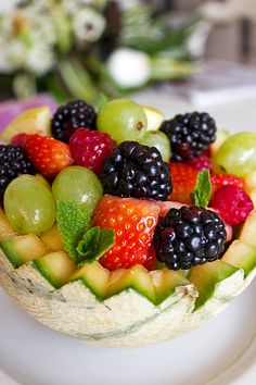 Fruit salad (melon, grapes, apple, strawberry, blackberries, raspberries) with lemon, honey and ginger syrup and small mint leaves for decoration