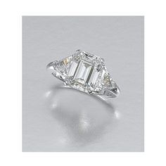 DIAMOND RING, TIFFANY & CO. Centring on a step-cut diamond weighing 5.00 carats between trilliant-cut diamond shoulders, size Q, maker's marks for Tiffany & Co, cased.