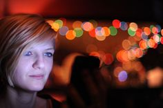 Subject lit by her phone ... more fairy lights in the background.  50mm @ f1.4 Nikon D700
