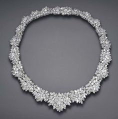 A DIAMOND NECKLACE Of flexible tapering design, composed of a graduated series of circular and marquise-cut diamond foliate clusters, mounted in platinum, 15¼ ins.