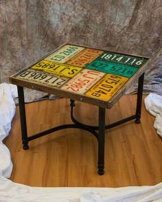 Vintage metal table, reclaimed pallet lumber border, repurposed license plate mounted on custom wood top. Top sealed with resin.