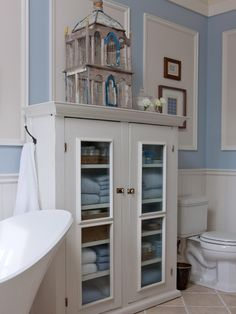 A vintage birdcage sits atop a white, wood hutch in this cottage-style bathroom. Pale blue towels pick up the pale blue of the walls.