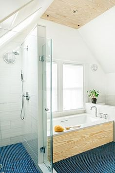 A tub with a view and a shower fit under the sloped ceiling of the Cambridge Project House master bath. Southern yellow pine adds a warm touch to the tub surround and the vanity toekick.   Photo: Anthony Tieuli   thisoldhouse.com