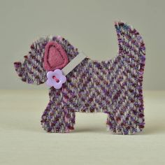 A beautiful handmade Harris Tweed dog brooch that makes a perfect gift for dog lovers.The dog brooch is available in pink/purple check, blue herringbone and purple herringbone. Please see the photographs above which show the three different tweed fabrics available. Due to the large check pattern of the fabric your brooch may vary slightly from those depicted in the photographs.The Harris Tweed used to make this brooch is hand woven in the Outer Hebrides using traditional methods. It is made…