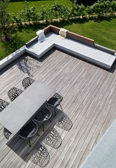 Lovely large wooden terrace with a dining area with sculptural chairs and a lounge corner made as a granite plinth - very appealing!