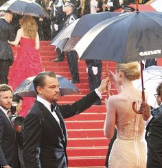 Such a gentleman! Leonardo DiCaprio gave up his umbrella while standing in the pouring rain to protect Elizabeth Debicki's designer dress at the Cannes Film Festival 2013 opening ceremony. via dailymail.co.uk