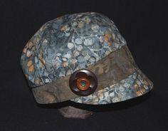 Lovely hat combining two batik fabrics and stacked buttons. Designer not yet offering pattern for sale. Boo.