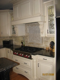 Travertine subway tile backsplash with basket weave above range