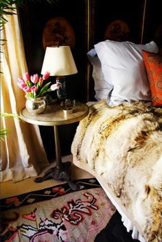 I love the fur throw/coverlet & vintage rug. I think I would like  a real fur throw at the bottom of the bed or sheepskin rugs  on each side of the bed.