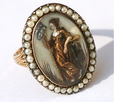 Britannia gold Mourning Ring , dated 1784, containing a mourning miniature executed in an unusual medium. The miniature is enclosed in a domed crystal and bordered by pearls. To reverse, the ring is inscribed : Capt'n John Cook Obt 3rd Feb 1784 At 50.