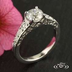 Custom platinum mounting with old mine cut diamond and bead set single cut diamonds on the sides. Geometric cut out pattern and side face of shoulders give the ring a delicate look.