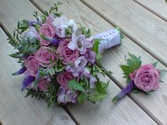 A bouquet of coolwater roses, lilac freesia and purple veronica