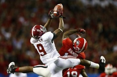 Alabama wide receiver Amari Cooper (9) hangs on to a pass over the defense of Georgia safety Bacarri Rambo (18) during the second quarter of the NCAA SEC college football championship in Atlanta, Georgia, December 1, 2012. REUTERS-Chris Keane