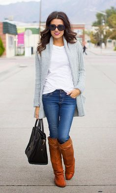 White blouse with grey warm open long sweater and blue casual jeans and black leather hand bag and brown leather long boots