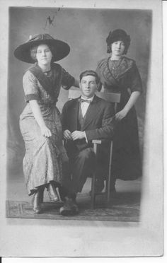 Clara Ellingson standing on right, her sister, Nora Grimstead, is sitting on chair arm beside her husband Ted.