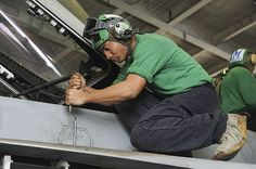 Aviation Electronics Technician 3rd Class Garnett Carter from Okinawa, Japan, assigned to the Pukin Dogs of Strike Fighter Squadron (VFA) 143, removes a panel while performing an inspection on an F/A-18E Super Hornet aboard the aircraft carrier USS Dwight D. Eisenhower (CVN 69). Dwight D. Eisenhower is deployed to the U.S. 5th Fleet area of responsibility conducting maritime security operations, theater security cooperation efforts and support missions as part of Operation Enduring Freedom.