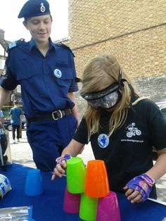A young girl tries to stack plastic cups while impaired by wearing a Drunk Busters Goggle, which are available in 10 different styles and are backed with a 5 year warranty.  www.drunkbusters.com