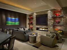 This beautiful contemporary living room has an entire stone wall with a gas-burning fireplace tucked in a crevice below the television. The walls are inset on either side of the fireplace, with wooden display shelves.