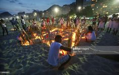 The faithful gather for a ceremony honoring Iemanja, Goddess of the Sea, as part of traditional New Year's celebrations on the sands of Copacabana beach on December 28, 2013 in Rio de Janeiro, Brazil. Iemanja is a goddess from the African Candomble religion brought to Brazil by West African slaves. Devotees traditionally mark the day dressed in white while carrying a statue of Iemanja to the beach along with lighting candles and tossing flowers and other offerings into the sea.