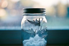 attempt to make this by making 2 paper birds... hang with fishing line from the top of the mason jar and put cotton balls on the bottom