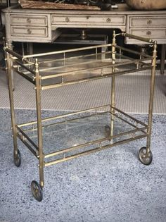 A mid-century Brass and Glass drinks trolley on castors