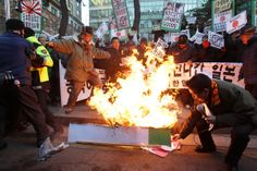 South Korean conservative burn a Japanese flag and effigy of Japanese Prime Minister Shinzo Abe during a anti-Japan rally in front of the Ja...