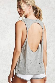 A knit tank top featuring an allover distressed effect, a round neck, and a twisted open back design.