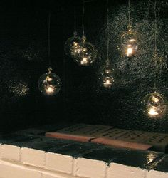 put softboard up inside the chimney of a non-working fireplace.  Then wrap wire around toothpicks slipped under the softboard. From the wires, hang glass balls with tealights in