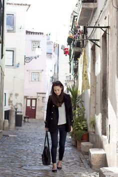 Nisi is wearing a Zara military jacket, striped longsleever from COS, Topshop skinny jeans, Zara patent leather flats, Zara studded shopper and sunglasses from Ralph Lauren in Alfama, Lisbon, Portugal - teetharejade.com