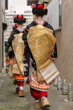Maiko in Miyagawa-cho pass by plastic bottles placed to ward off cats during their New Year's Greetings, Japan