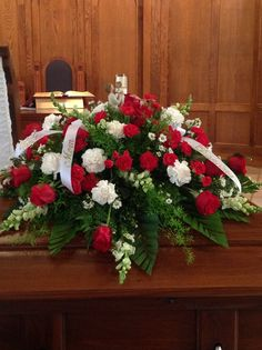 Traditional red and white casket spray.With a Willow tree angel and a hummingbird in the spray.