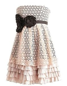 Eyelet Extravaganza Dress: Features a high-quality ivory shell crowning a beautiful beige underlay, black satin origami-style rosettes offsetting a contrast banded waist, and a gorgeous tiered ruffled princess hem to finish.