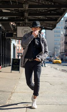 Nail off-duty dressing with this combination of a black denim jacket and black jeans. Dress down this getup with white high top sneakers.  Shop this look for $138:  http://lookastic.com/men/looks/hat-denim-jacket-cardigan-jeans-high-top-sneakers/6460  — Black Wool Hat  — Black Denim Jacket  — Charcoal Knit Cardigan  — Black Jeans  — White High Top Sneakers