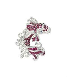 A RUBY AND DIAMOND BROOCH, BY GRAFF Designed as a circular-cut diamond koi with circular-cut ruby accents on the body, fins and tail, swimming within openwork water motifs lined with circular-cut diamonds and collet-set pear and circular-cut diamond droplets, 2 3/4 ins., mounted in 18k white gold Signed Graff,