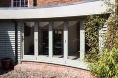 Burton Overy - Curved Folding Sliding Doors - This project design was for a concave curved folding sliding door system. This was to allow access into a small courtyard from an extension, created to join a period house to outbuildings. A 5 door leaf system was crafted in hardwood with all the door leafs effortlessly opening in one direction, to allow for a free flow into the courtyard.