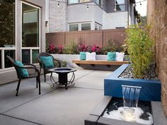A blue block planter doubles as a water feature in this small backyard space. Two chairs adorned with fuzzy blue throw pillows create a sitting area by the fire pit.